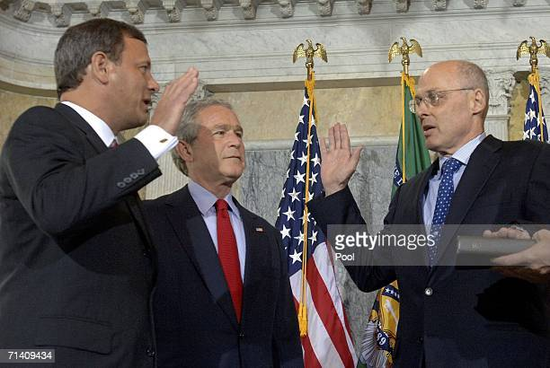 Investment banker Henry Paulson is sworn in by Chief Justice John Roberts as US President George W Bush looks on during a ceremony at the Treasury...