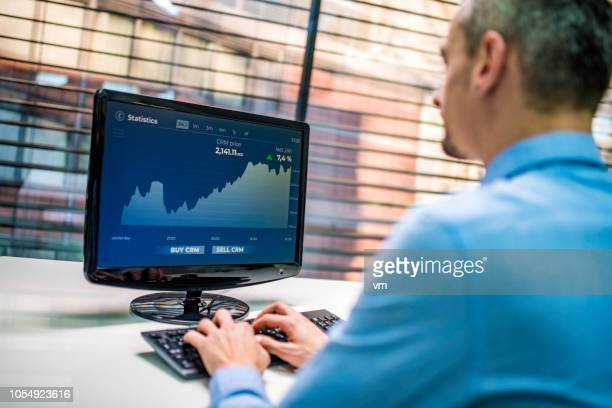 investment manager analyzing graph on his computer - financial analyst stock pictures, royalty-free photos & images