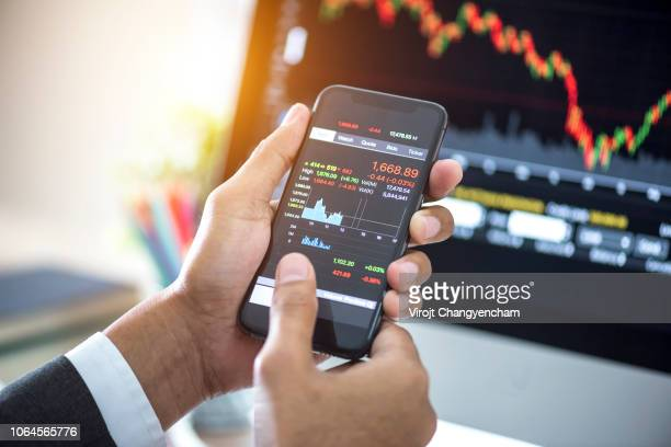 investor analyzing stock market investments with financial dashboard on smartphone and computer screens - kapitell stock-fotos und bilder