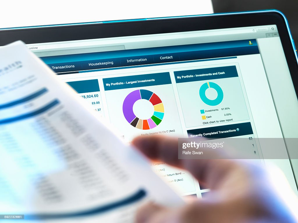 Investor checking performance of financial portfolio online whilst reviewing investment statement : Stock Photo