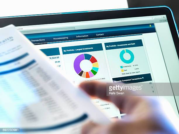 investor checking performance of financial portfolio online whilst reviewing investment statement - savings stock pictures, royalty-free photos & images