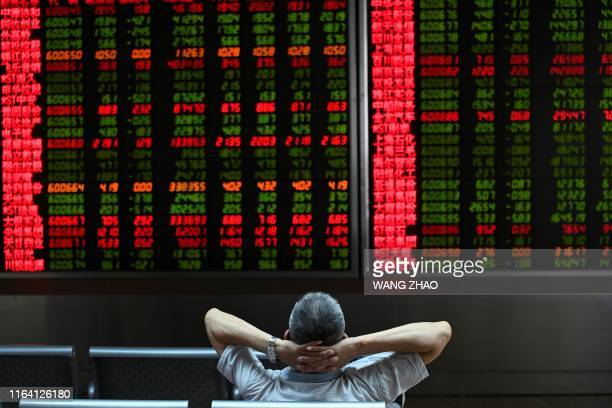 A Investor looks at screens showing stock market movements at a securities company in Beijing on August 26 2019 Asian equity markets tanked and the...