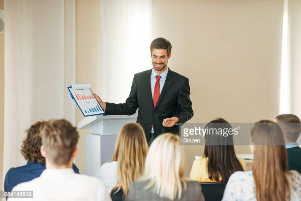 Investor showing financial figures on seminar for economists