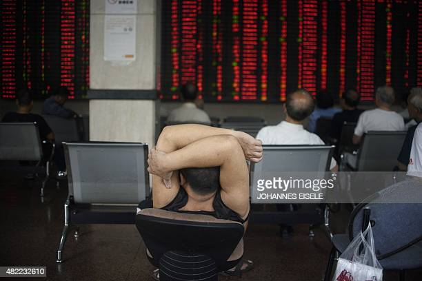 Investor sit while monitoring screens showing stock market movements at a brokerage house in Shanghai on July 29 2015 An 848 percent plunge on July...