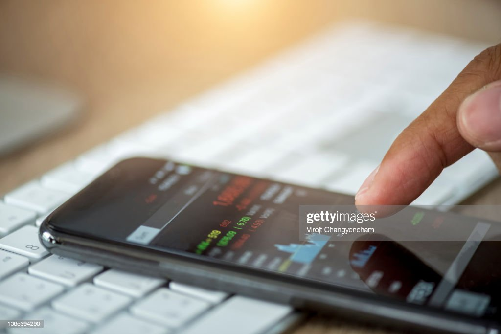 Investor using mobile device check stock market data. : Stock Photo