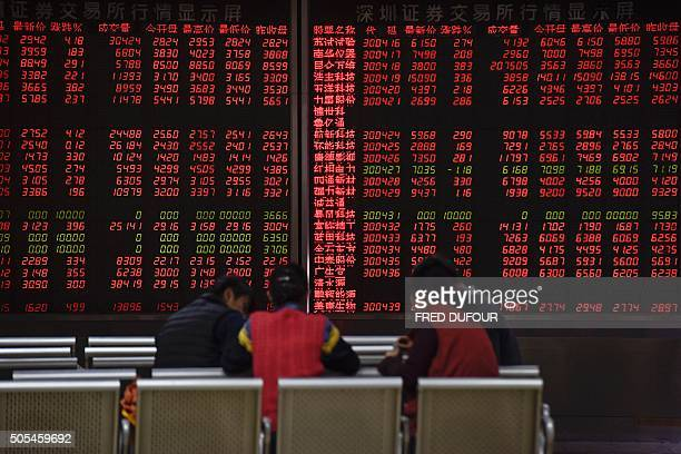 Investors are seen in front of an electronic board showing stock information at a brokerage house in Beijing on January 18 2016 Shanghai stocks ended...