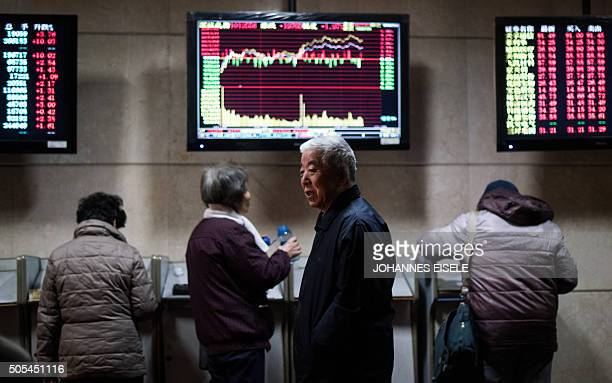 Investors are seen in front of electronic boards showing stock information at a brokerage house in Shanghai on January 18 2016 Shanghai stocks ended...