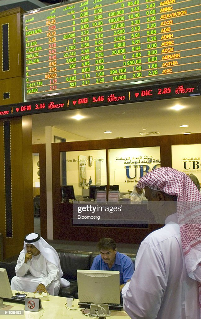 Investors check their stocks while on the floor at the Dubai    News