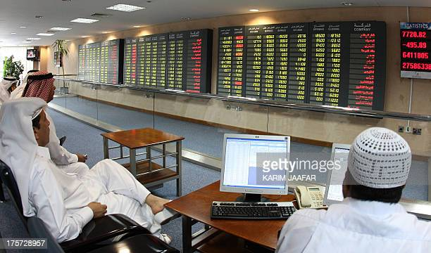 Investors follow the stock market activity on monitors at the Doha Securities Market in Doha on September 16 2008 Global equities tumbled for a...