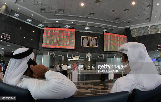 Investors follow the stock market activity on monitors at the Doha Securities Market in the Qatari capital on September 16 2008 Global equities...