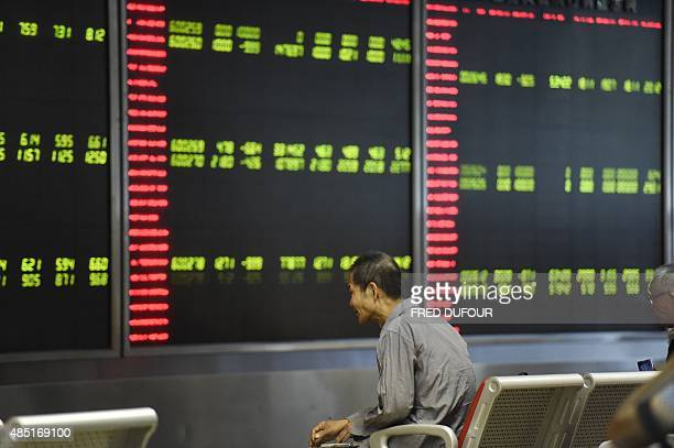 Investors look at screens showing stock market movements at a securities company in Beijing on August 25 2015 Equity markets convulsed on August 25...