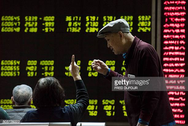 Investors look at screens showing stock market movements at a securities company in Beijing on January 7 2016 Chinese markets were suspended on...
