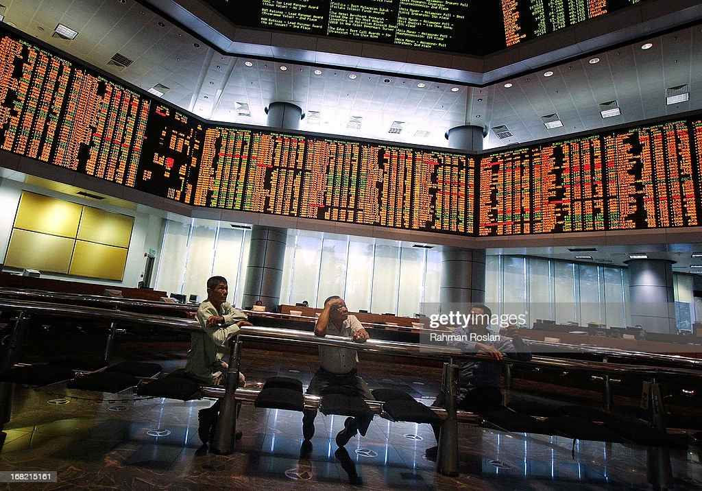 Investors monitor the stock prices displayed on the Kuala Lumpur Composite Index (KLCI) at the RHB Investment Bank trading gallery on May 7, 2013 in Kuala Lumpur, Malaysia. Malaysia's stock market has risen to an all time record sparked by Barisan National's victory on the 13th general election.