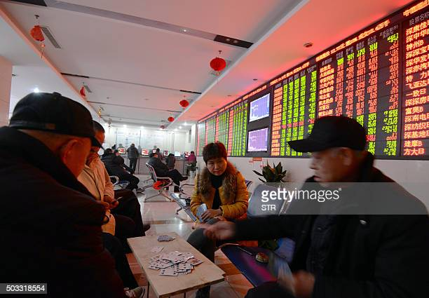 Investors play cards in a stock firm in Fuyang east China's Anhui province on January 4 2016 Trading on the Shanghai and Shenzhen stock exchanges was...