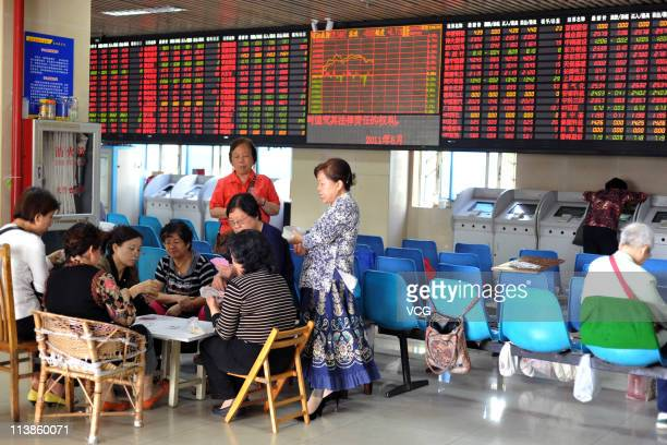 Investors play poker at a stock exchange hall on May 9, 2011 in Shanghai, China. The power companies and train markers led Chinese stocks rebounding...