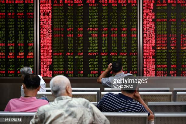 Investors rest on a chair in front of screens showing stock market movements at a securities company in Beijing on August 26 2019 Asian equity...