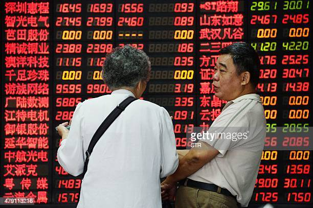 Investors talk in front of a board displaying share prices at a security firm in Shanghai on July 1 2015 Shanghai shares closed down more than five...