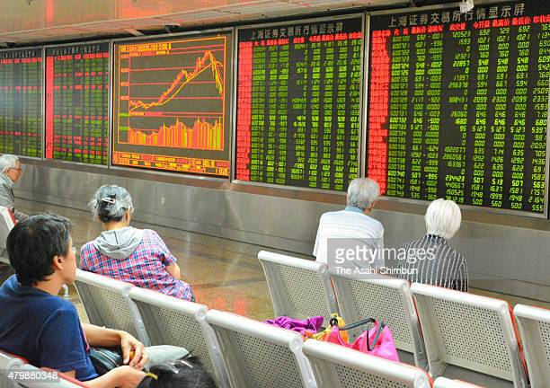 Investors watch electric boards displaying the stock price at an security company on July 8 2015 in Beijing China