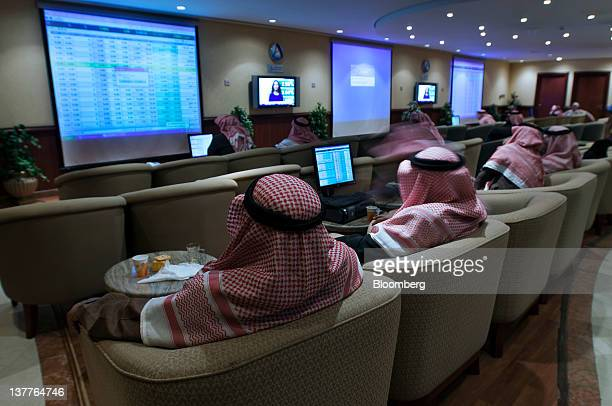 Investors watch share price movements displayed on screens in a hall at ANB Invest the investment arm of the Arab National Bank in Riyadh Saudi...
