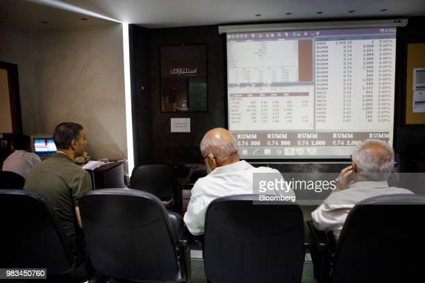 Investors watch trading screens at the International Financial Center at the Housing Bank Complex in Amman Jordan on Thursday June 21 2018 President...