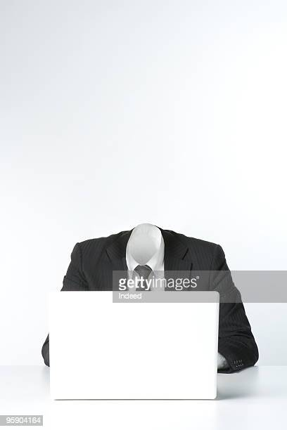 Invisible businessman using laptop