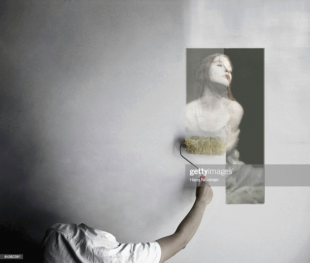 Invisible man erasing an image from the wall : Stock Photo