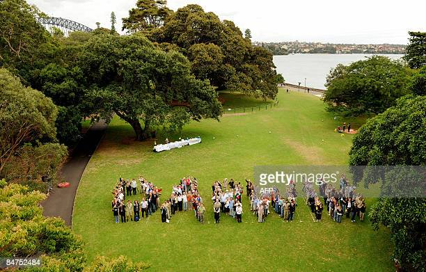 Invited guests group together to spell out the word Darwin in celebration of naturalist Charles Darwin at the Sydney Royal Botanic Gardens on...