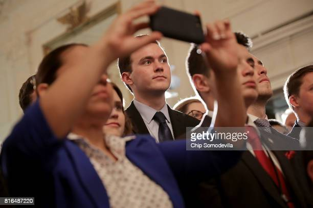Invited guests listen to US President Donald Trump deliver remarks during a Made in America product showcase in the East Room of the White House July...