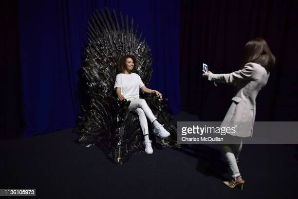 Invited guests pose on the Iron Throne at the Game Of Thrones: The Touring Exhibition launch at Titanic Exhibition Centre on April 10, 2019 in...