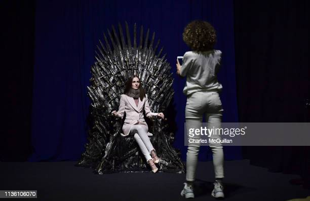 Invited guests pose on the Iron Throne at the Game Of Thrones The Touring Exhibition launch at Titanic Exhibition Centre on April 10 2019 in Belfast...