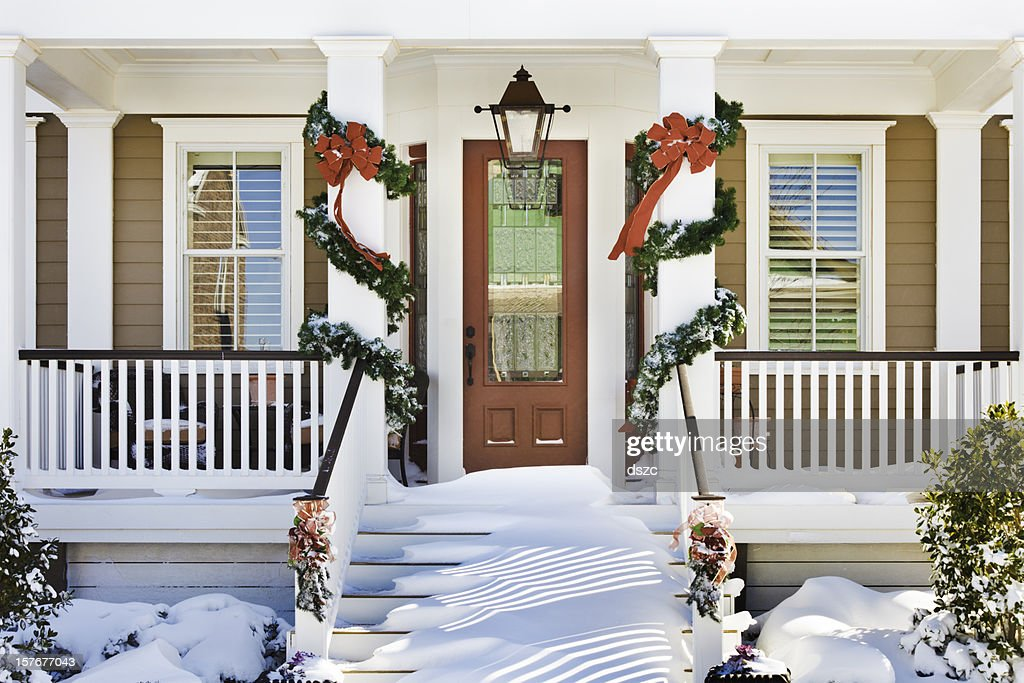 inviting Christmas front doorway with snow on porch stairs : Stock Photo