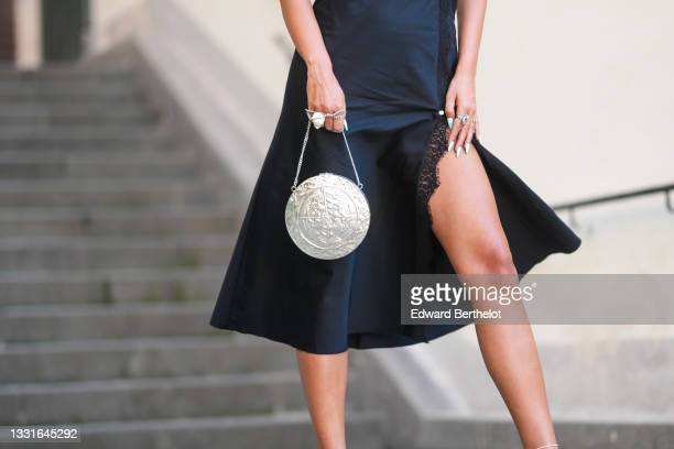 Ioana Visanescu wears a black satin and lace on the borders slit / split midi dress, a silver shiny circle embossed handbag, silver rings, after the...
