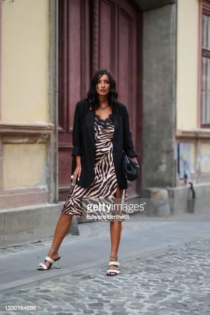 Ioana Visanescu wears a necklace, a black oversized blazer jacket, a black and beige zebra pattern printed midi slit dress with embroidery, a black...