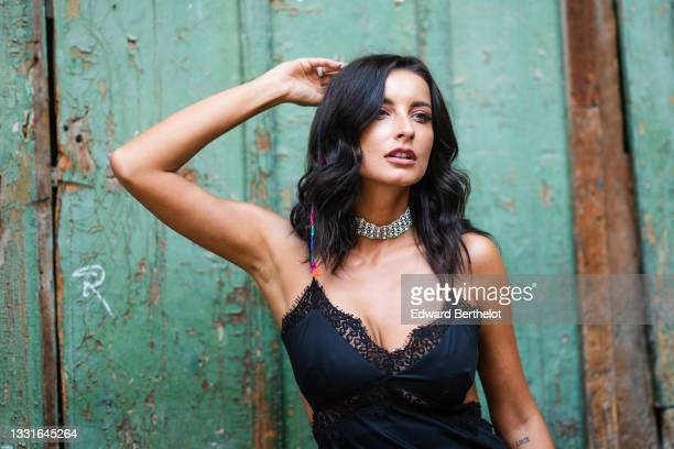Ioana Visanescu wears silver earrings, a silver and rhinestones necklace, a black satin cut-out / lace on the borders / V-neck / tank-top / dress,...