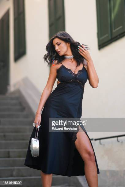 Ioana Visanescu wears silver earrings, a silver and rhinestones necklace, a black satin cut-out / lace on the borders / V-neck / tank-top / split...
