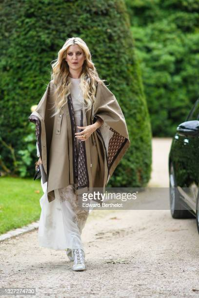 Ioanna Gika wears a white with beige print pattern long flowing dress, a beige oversized cloak with blue and beige Dior Oblique Jacquard interior...