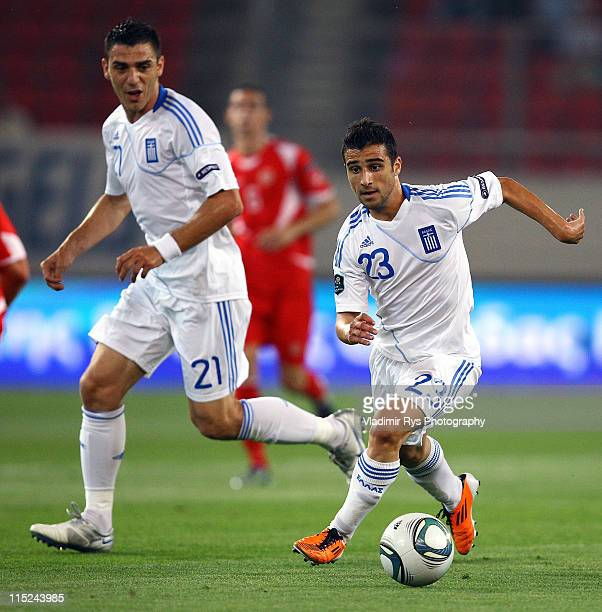 Ioannis Fetfatzidis controls the ball as his team mate Konstantinos Katsouranis of Greece looks on during the EURO 2012 group F qualifying match...