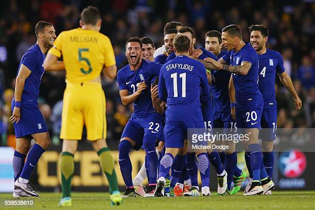 Ioannis Maniatis of Greece is mobbed by teammates as he celebrates a goal during the International Friendly match between the Australian Socceroos...