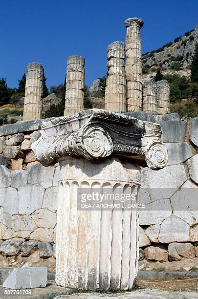 Ionic capital and the temple of Apollo in the background archaeological site of Delphi Greece Greek civilisation
