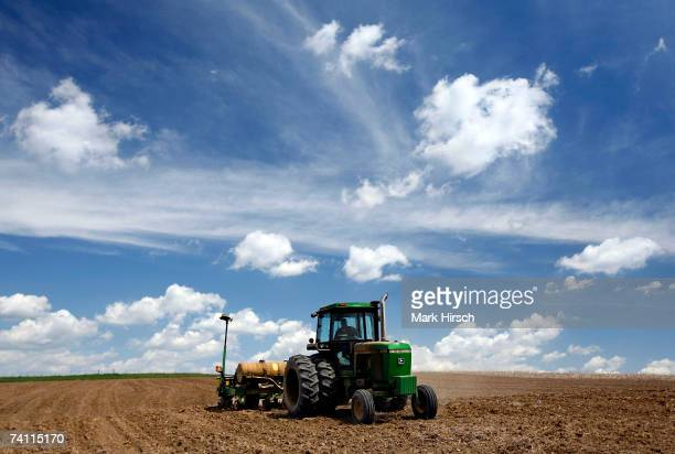 Iowa farmer Ernie George Goebel pulls a corn planter behind his John Deere tractor while planting corn in a field on the farm he was raised on May 9...