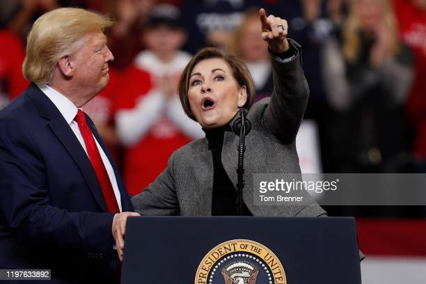 Iowa Governor Kim Reynolds points to the audience while speaking beside President Donald Trump during a campaign rally inside of the Knapp Center...