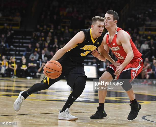 Iowa guard Jordan Bohannon drives past Ohio State guard Andrew Dakich during a Big Ten Conference basketball game between the Ohio State Buckeyes and...