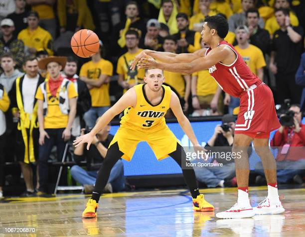 Iowa Hawkeyes guard Jordan Bohannon looks on as Wisconsin Badgers guard D'Mitrik Trice passes the ball during a Big Ten Conference college basketball...