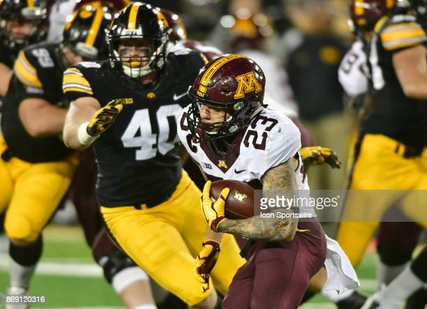 Iowa Hawkeyes' right end Parker Hesse gets ready to tackle Minnesota Gophers tailback Shannon Brooks during a Big Ten Conference football game...