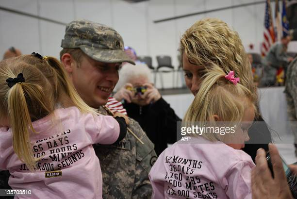 OBERMAN = Iowa National Guarsman James Hauswirth greets his daughters and girlfriend Dawn Gaule for the first time in a year at a welcome home...