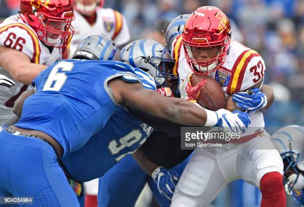 Iowa State Cyclones running back David Montgomery tries to break free of two Memphis Tigers defenders during the first quarter of a NCAA college...