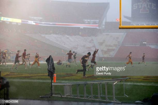 Iowa State Cyclones students run onto the football field during a thunderstorm at Jack Trice Stadium on September 14, 2019 in Ames, Iowa. The game...