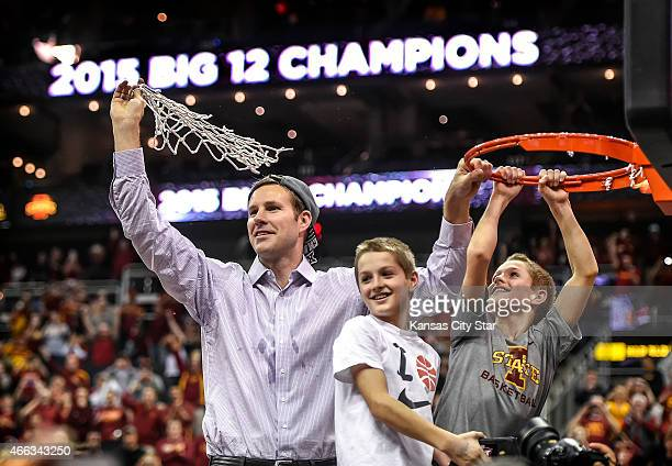 Iowa State head coach Fred Hoiberg holds up the net with his twin sons Sam and Charlie following a 7066 victory against Kansas in the finals of the...