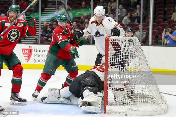 Iowa Wild center Pat Cannone points to the goal as the puck made its way underneath Cleveland Monsters goalie Matiss Kivlenieks for a goal during the...