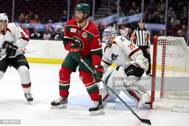 Iowa Wild left wing Ryan Malone screens Cleveland Monsters goalie Matiss Kivlenieks as he looks for a pass in front of the net during the first...